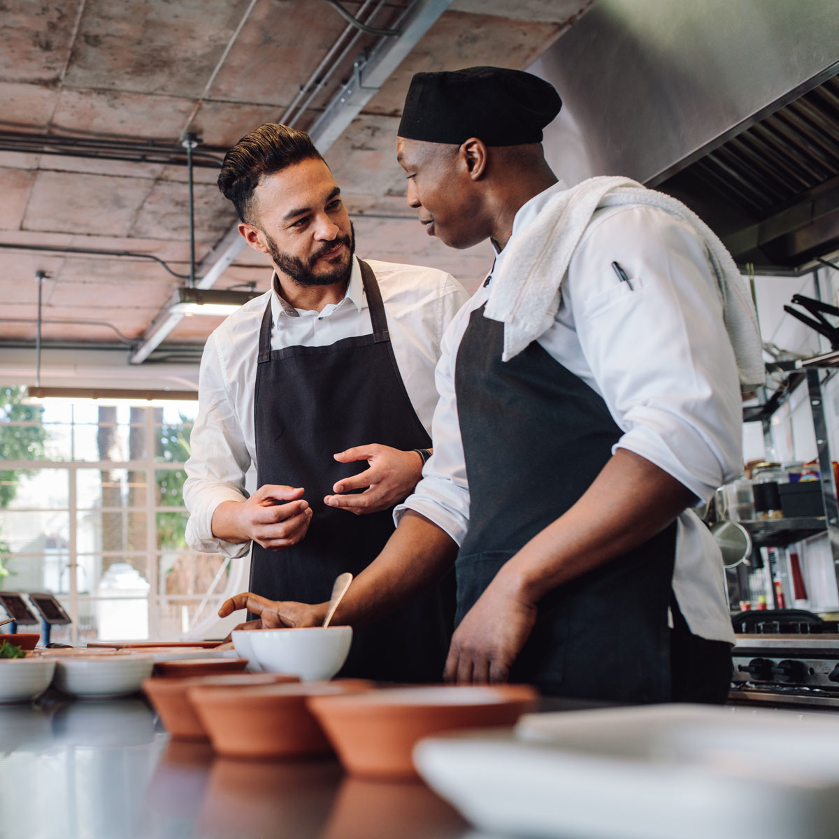 Business owner and chef working in kitchen