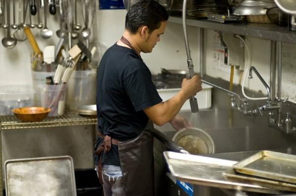 Man rinsing dishes in restaurant kitchen