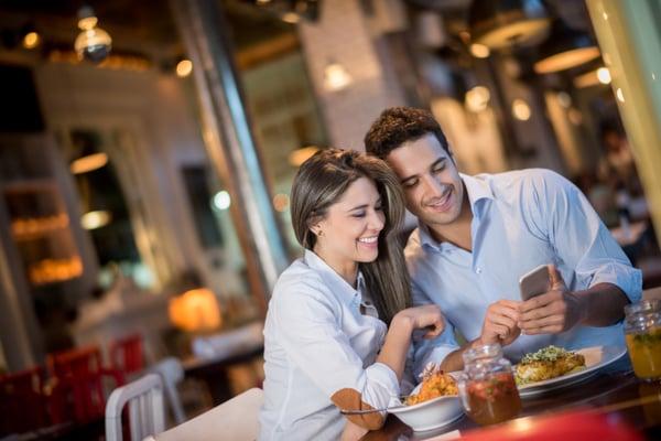 Man and woman at restaurant looking at phone